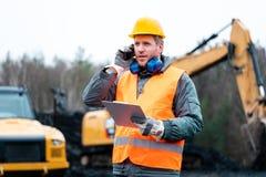 Portret van een steengroevearbeider die zich voor graafwerktuig bevinden stock foto