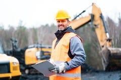 Portret van een steengroevearbeider die zich voor graafwerktuig bevinden stock fotografie