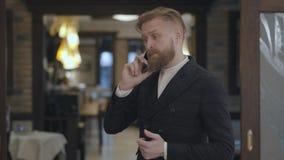 Portret van een succesvolle bedrijfsmens met een rode baard die op zijn cel in een dure restaurant of een koffie spreken stock video