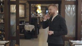 Portret van een succesvolle bedrijfsmens in modieuze glazen met een rode baard die op zijn cel in een duur restaurant spreken stock video