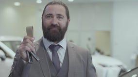 Portret van een succesvolle gebaarde bedrijfsmens in een pak die de sleutel van een luxeauto tonen die de camera onderzoeken stock footage