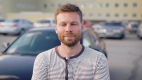 Portret van een succesvolle mens die zich door zijn auto op het het buitenparkeerterrein en glimlachen bevinden stock video