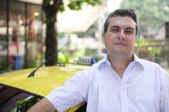 Portret van een taxibestuurder met cabine royalty-vrije stock afbeeldingen