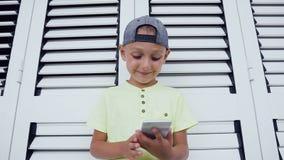 Portret van een tevreden leuke weinig jong geitje speeldiespelen op smartphone over witte achtergrond worden geïsoleerd Kind die  stock video