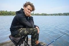Portret van een tiener die op de bank van de rivier of het meer vissen Leuke jongen met krullend haar royalty-vrije stock afbeeldingen