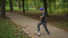 Portret van een tiener die op een pennyboard danst Een kerel van Europese verschijning heeft en pret die dansen glimlachen stock footage