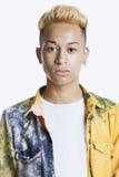 Portret van een in tiener met losgeknoopt overhemd over grijze achtergrond Stock Foto's