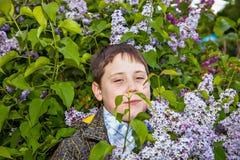 Portret van een tiener tegen de achtergrond van een tot bloei komende lilac struik Royalty-vrije Stock Afbeelding