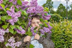 Portret van een tiener tegen de achtergrond van een tot bloei komende lilac struik Royalty-vrije Stock Foto