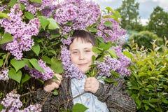 Portret van een tiener tegen de achtergrond van een tot bloei komende lilac struik Stock Foto's