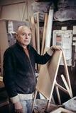 Portret van een timmerman met een nieuwe schildersezel royalty-vrije stock afbeelding