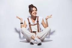 Portret van een toevallige gelukkige vrouwenzitting op de vloer op witte achtergrond royalty-vrije stock foto