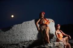 Portret van een twee mooie paarmeisjes op de kust bij nigh stock foto's