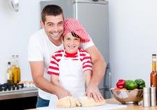 Portret van een vader en zijn zoon die een maaltijd voorbereiden stock foto's