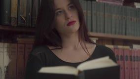 Portret van een vermoeide jonge student die met heldere make-up een boek in een bibliotheek lezen die zich voor boekenrek bevinde stock footage
