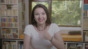 Portret van een verraste jonge vrouw die voor boekenkast glimlachen - stock video