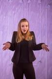 Portret van een verraste jonge vrouw in een zwart kostuum Royalty-vrije Stock Afbeelding