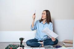 Portret van een verraste, in verwarring gebrachte vrouw op de vloer met een schroevedraaier en instructies voor de Assemblage van royalty-vrije stock fotografie
