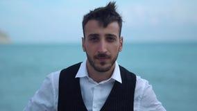 Portret van een verstoorde kerel die zich door het overzees bevinden De verstoorde gefrustreerde gebaarde mens zette zijn bruine  stock footage