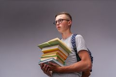 Portret van een verwarde jongensstudent met een rugzak en een stapel boeken in zijn handen, grappige positieve middelbare schoolt stock afbeeldingen