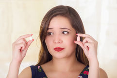 Portret van een verwarde vrouwenholding in zowel handen een zachte gelatine vaginale tablet of een zetpil, behandeling van ziekte stock fotografie