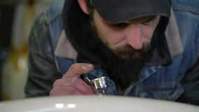 Portret van een volwassen gebaarde mens in een GLB met tatoegeringen die met luchtpenseel in workshop trekken stock videobeelden