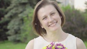 Portret van een vrij jonge vrouw die een boeket snuiven De mooie vrouw inhaleert de geur van bloemen stock footage
