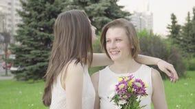 Portret van een vrij jonge vrouw die een boeket snuiven De mooie vrouw inhaleert de geur van bloemen stock videobeelden