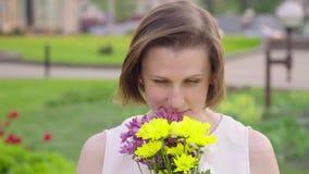 Portret van een vrij jonge vrouw die een boeket snuiven Mooie vrouwenglimlach stock video