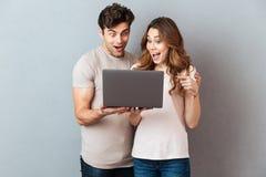 Portret van een vrolijk jong paar die laptop computer met behulp van stock foto