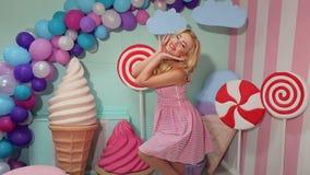 Portret van een vrolijk meisje in een roze gestreepte kleding op achtergrond van reusachtige snoepjes stock footage