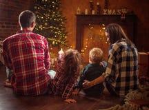 Portret van een vrolijke familie die in een de winteravond realxing stock fotografie