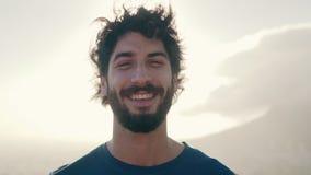Portret van een vrolijke jonge mens op zonnige dag stock video