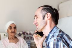 Portret van een vrolijke, knappe, Kaukasische mens met stoppelige baard die op mobiele telefoon spreken royalty-vrije stock afbeeldingen
