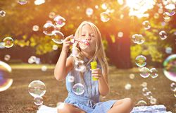 Portret van een vrolijke meisjes blazende zeepbels stock afbeeldingen