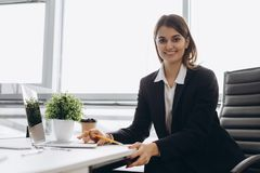 Portret van een vrolijke onderneemsterzitting bij de lijst in bureau en het bekijken camera stock fotografie
