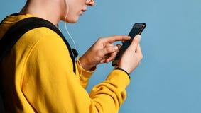 Portret van een vrolijke student die rugzak, in GLB en glazen dragen en smartphone over purpere achtergrond gebruiken stock fotografie
