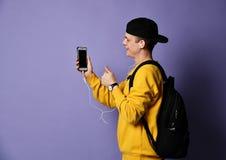 Portret van een vrolijke student die rugzak, in GLB en glazen dragen en smartphone over purpere achtergrond gebruiken royalty-vrije stock foto