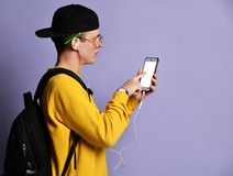 Portret van een vrolijke student die rugzak, in GLB en glazen dragen en smartphone over purpere achtergrond gebruiken stock foto