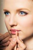 Portret van een vrouw die op lippenvoering zet. stock foto