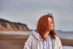 Portret van een vrouw die op middelbare leeftijd met rood haar langs de rivierbank lopen Zonnige de lenteochtend stock foto