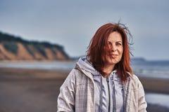 Portret van een vrouw die op middelbare leeftijd met rood haar langs de rivierbank lopen Zonnige de lenteochtend stock afbeelding
