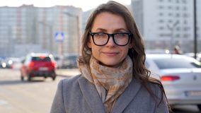 Portret van een vrouw in glazen met een kapsel en een neutrale make-up op een stads achtergrondclose-up stock footage