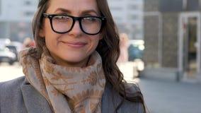 Portret van een vrouw in glazen met een kapsel en een neutrale make-up op een stads achtergrondclose-up stock video