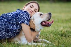 Portret van een vrouw met haar mooie hond die in openlucht liggen Stock Afbeeldingen