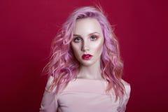 Portret van een vrouw met helder gekleurd vliegend haar, alle schaduwen van roze purple Haarkleuring, mooie lippen en make-up haa stock afbeelding