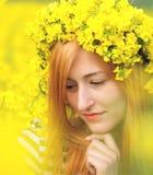 Portret van een vrouw met kroon van gele bloemen op het hoofd Stock Foto
