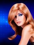 Portret van een vrouw met lange rode haren en maniermake-up Stock Foto