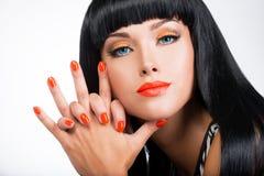 Portret van een vrouw met rode spijkers en glamourmake-up Stock Afbeelding