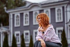 Portret van een vrouw op middelbare leeftijd met rood haar die glazen op een bewolkte dag dragen royalty-vrije stock fotografie